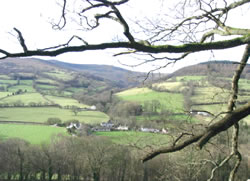 View of the meadows and pastures in the valley below, with the hills of the Brecon Beacons in the background